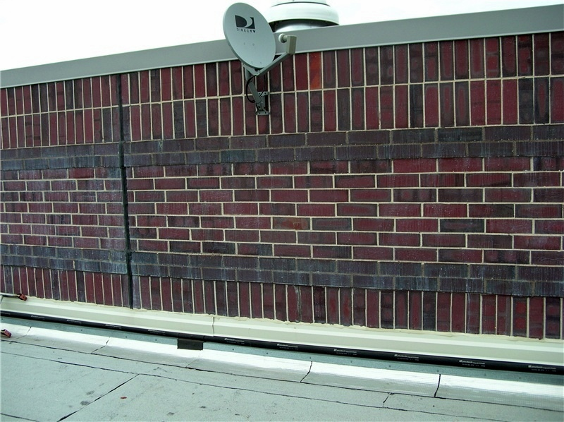 A brick rising wall between two roof areas.