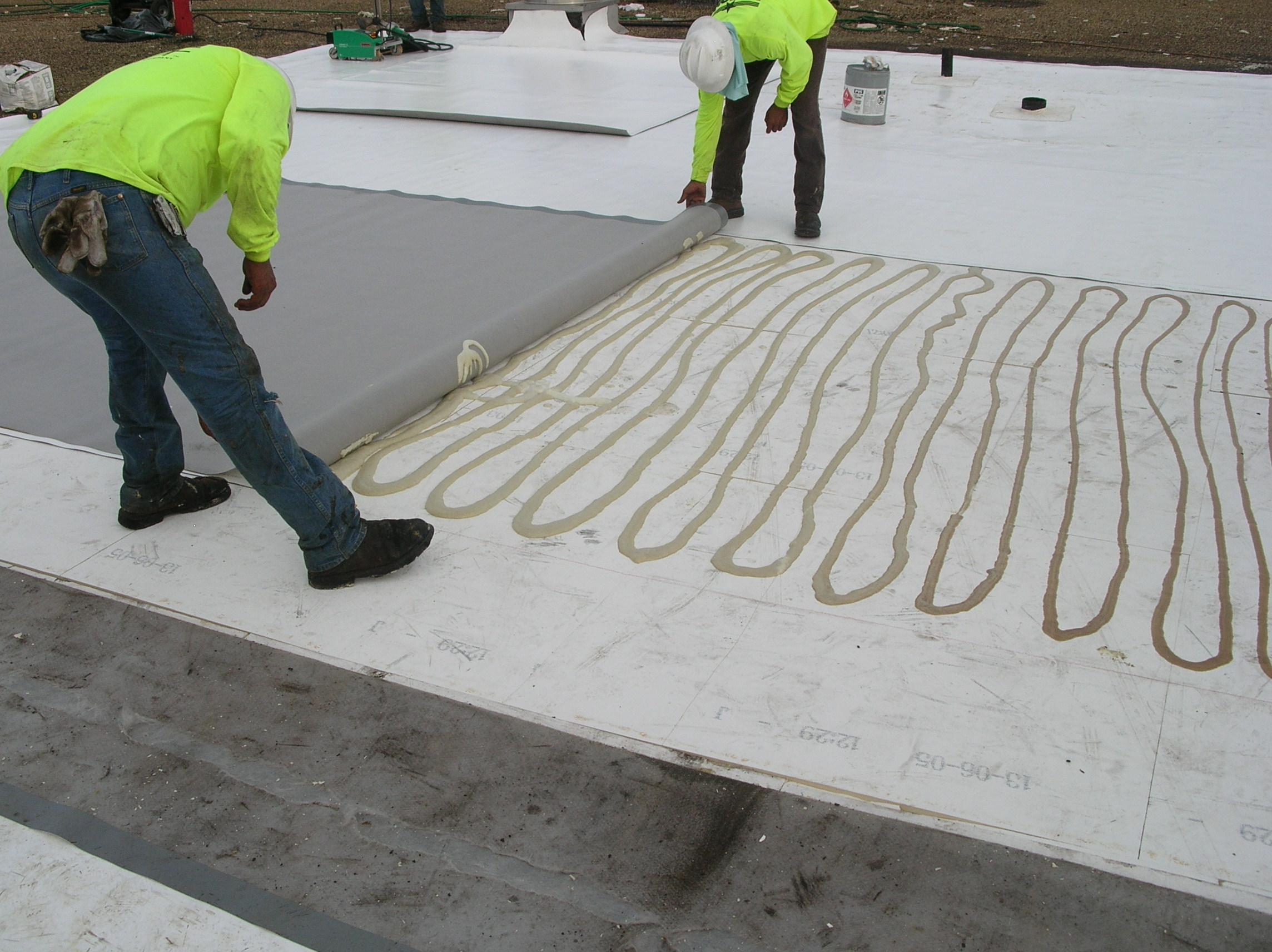 Installing a PVC field membrane sheet in adhesive