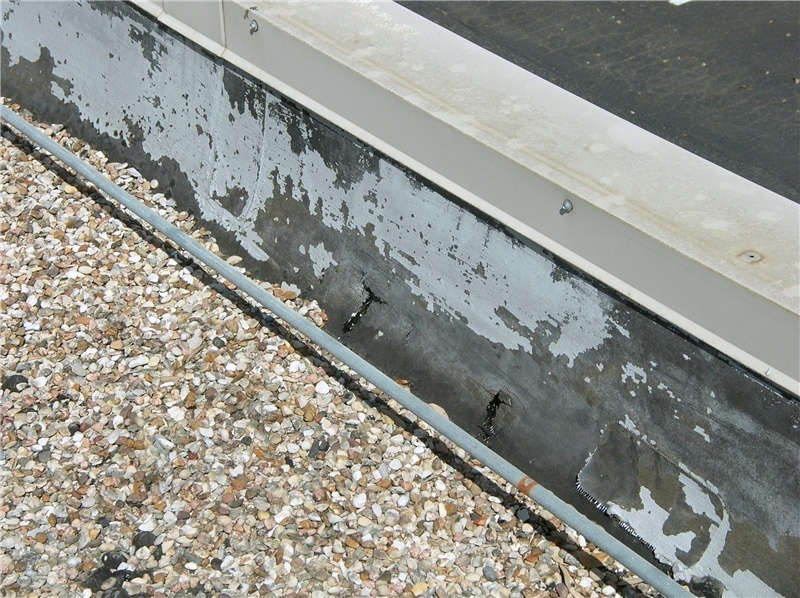 After a severe hail storm, two large punctures are visible at a blister in the base flashing on an aged built-up roof. As asphalt-based roof components age, they become more fragile and susceptible to hail damage.