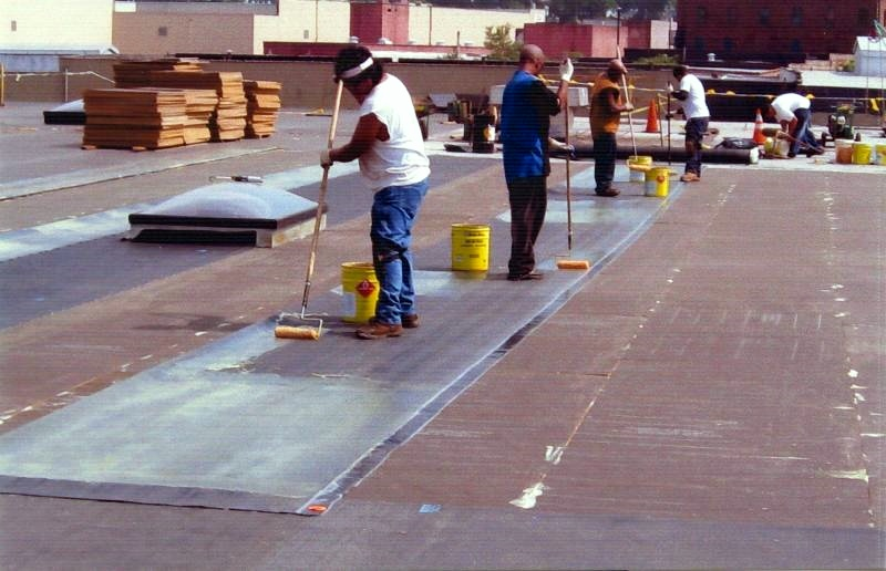 Applying adhesive to EPDM sheets during the installation of a fully-adhered EPDM roof.