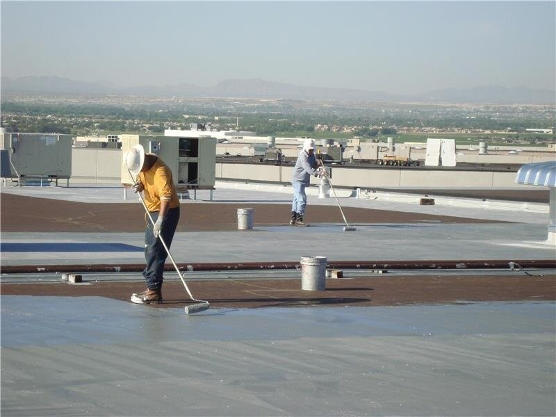 Applying an aluminized roof coating to a new smooth-surfaced asphalt built-up roof.