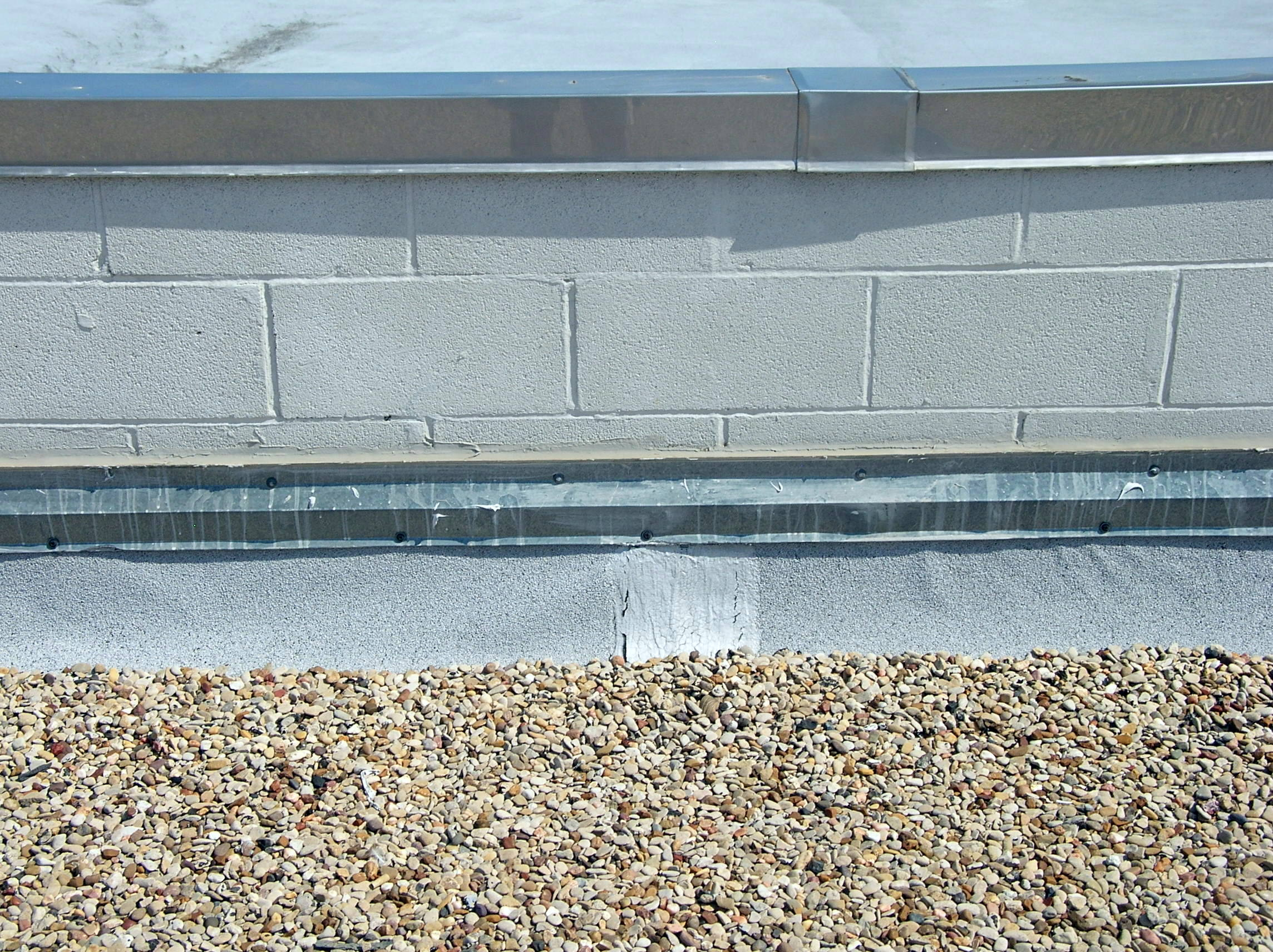 A coated concrete masonry unit parapet wall with stainless steel coping, modified bitumen base flashing, and surface-mounted metal counter-flashing.