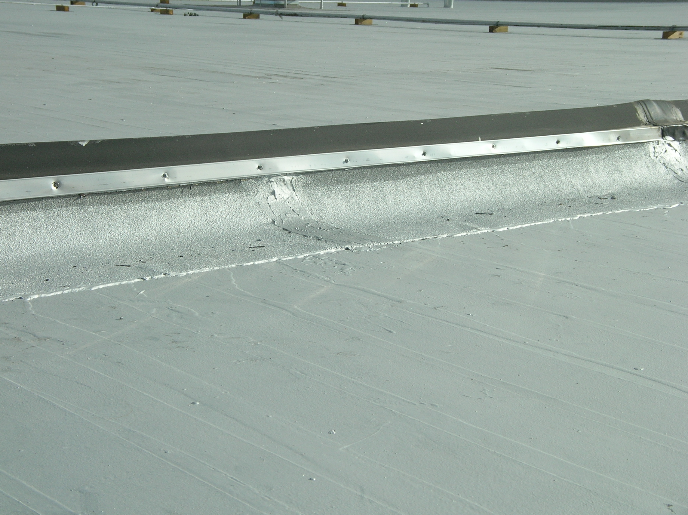 View of a curbed expansion joint between two roof sections.