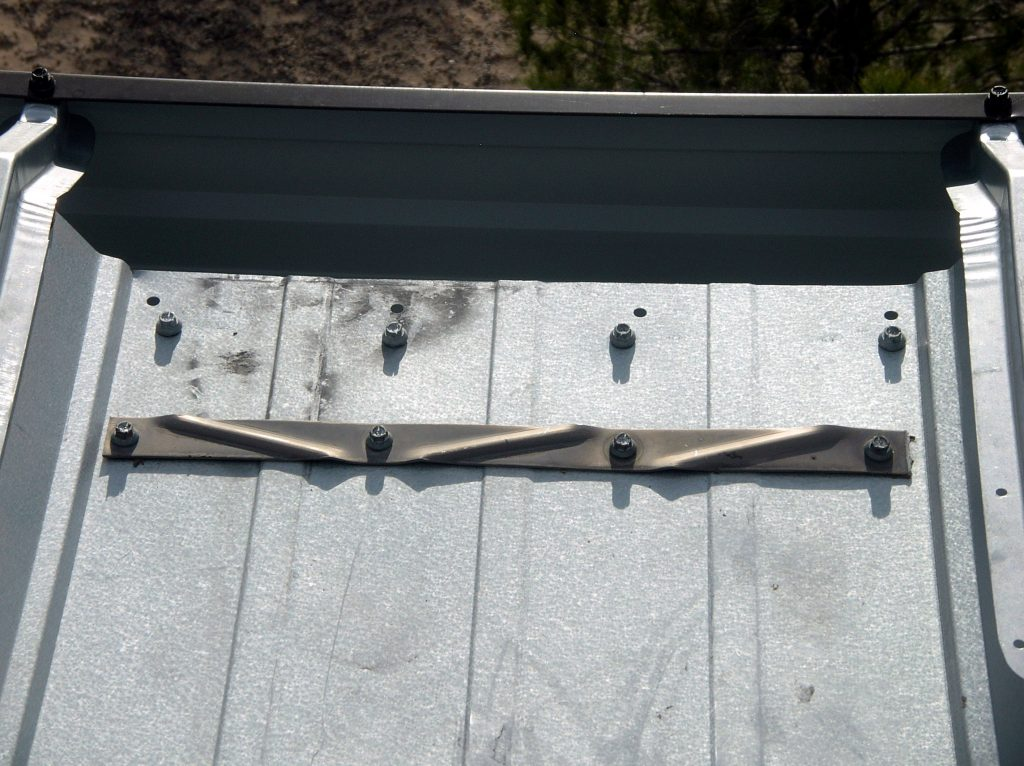 Fasteners at the gutter edge of a metal panel roof.