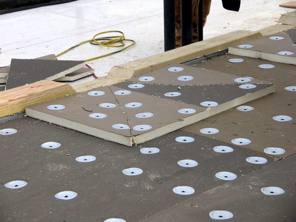 Fasteners with fastener plates securing polyiso insulation. (Yes, that is the FM-approved fastener pattern. It's a 40-story building.)