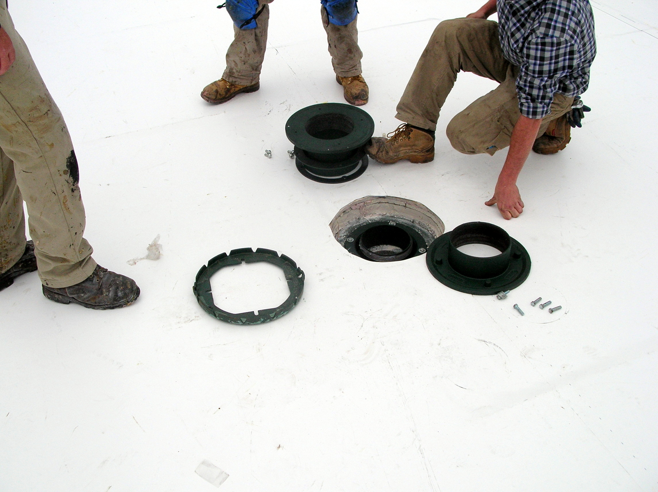 Installing a roof drain on a PVC roof.