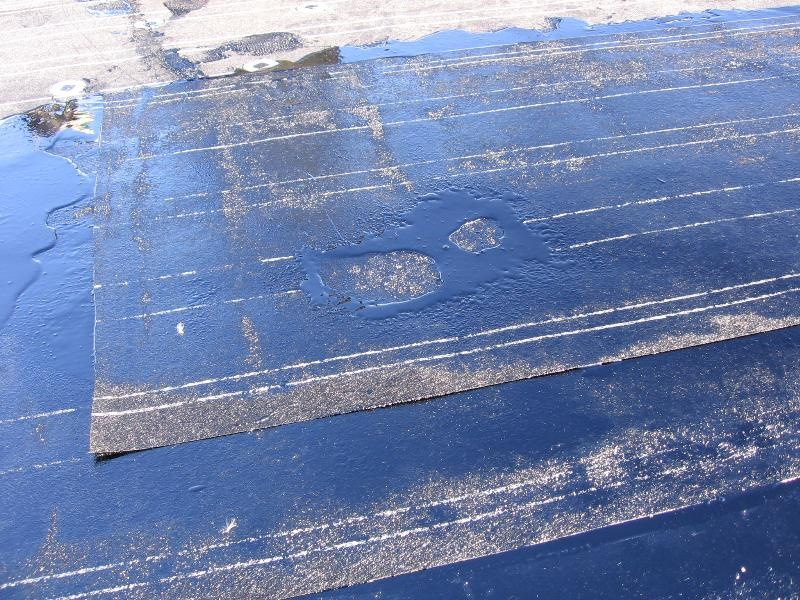Built-up roof installation: Layers of roofing felts and hot-applied asphalt make up this built-up roof membrane.