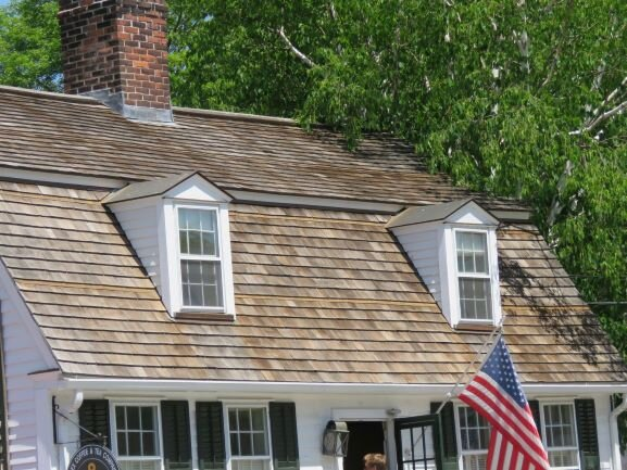 A cedar shingle roof like this one can last up to 40 years if it's taken care of properly. Those tree branches are going to be a problem, as the shade keeps the shingles from drying out properly, which can result in rot and undesirable growths.