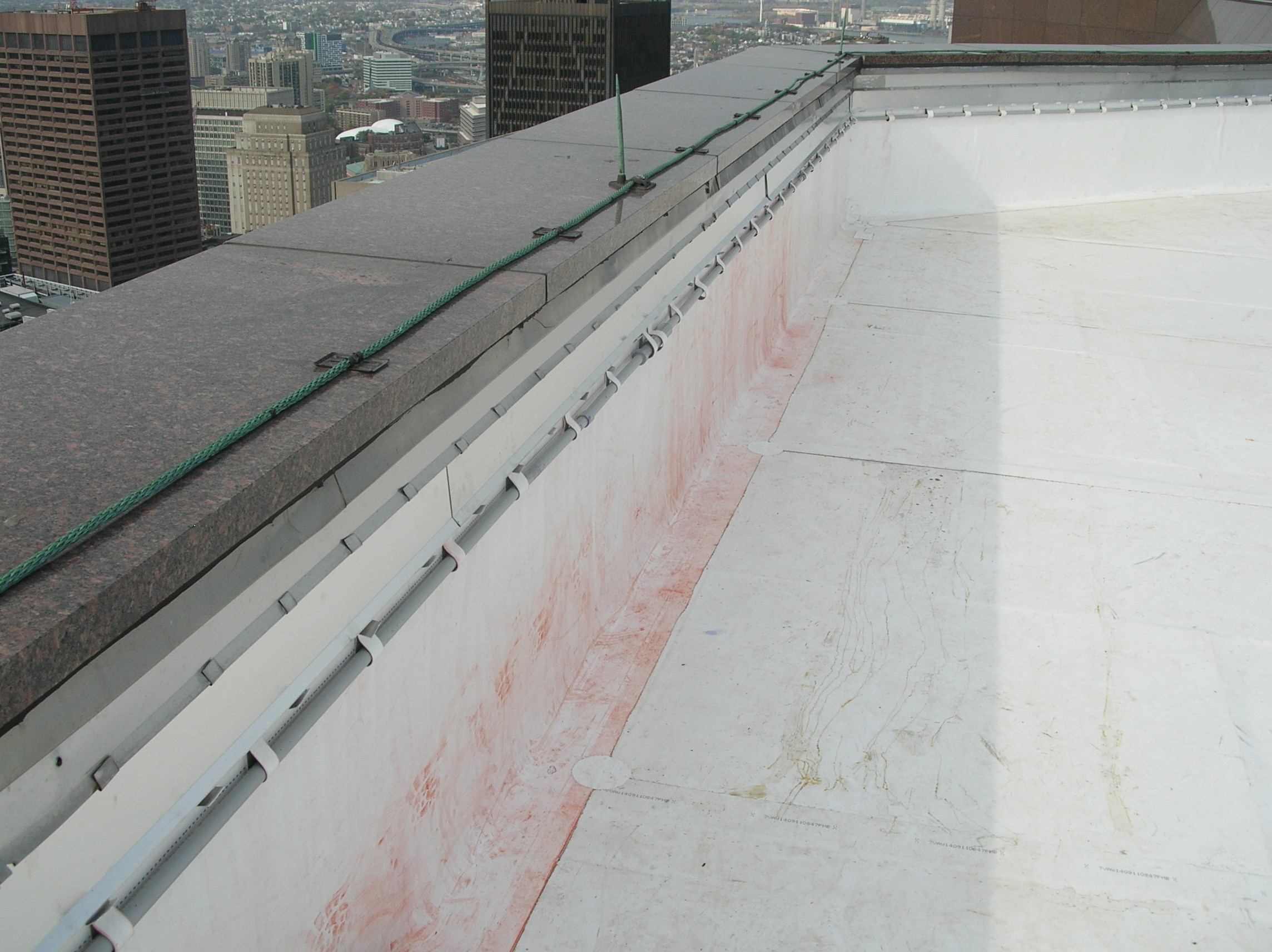 Natural stone (polished granite) coping with lightning protection system on a skyscraper roof parapet wall.