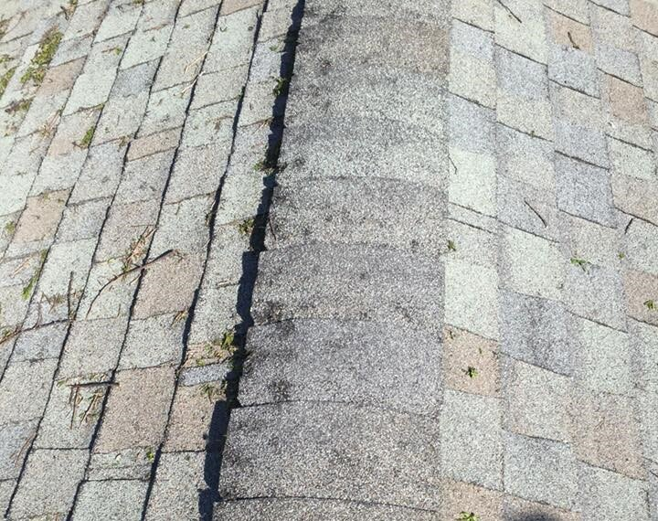 Hail-damaged asphalt shingles. You can see shingles with broken corners, missing ceramic granules at impact points, and wind-blown debris.