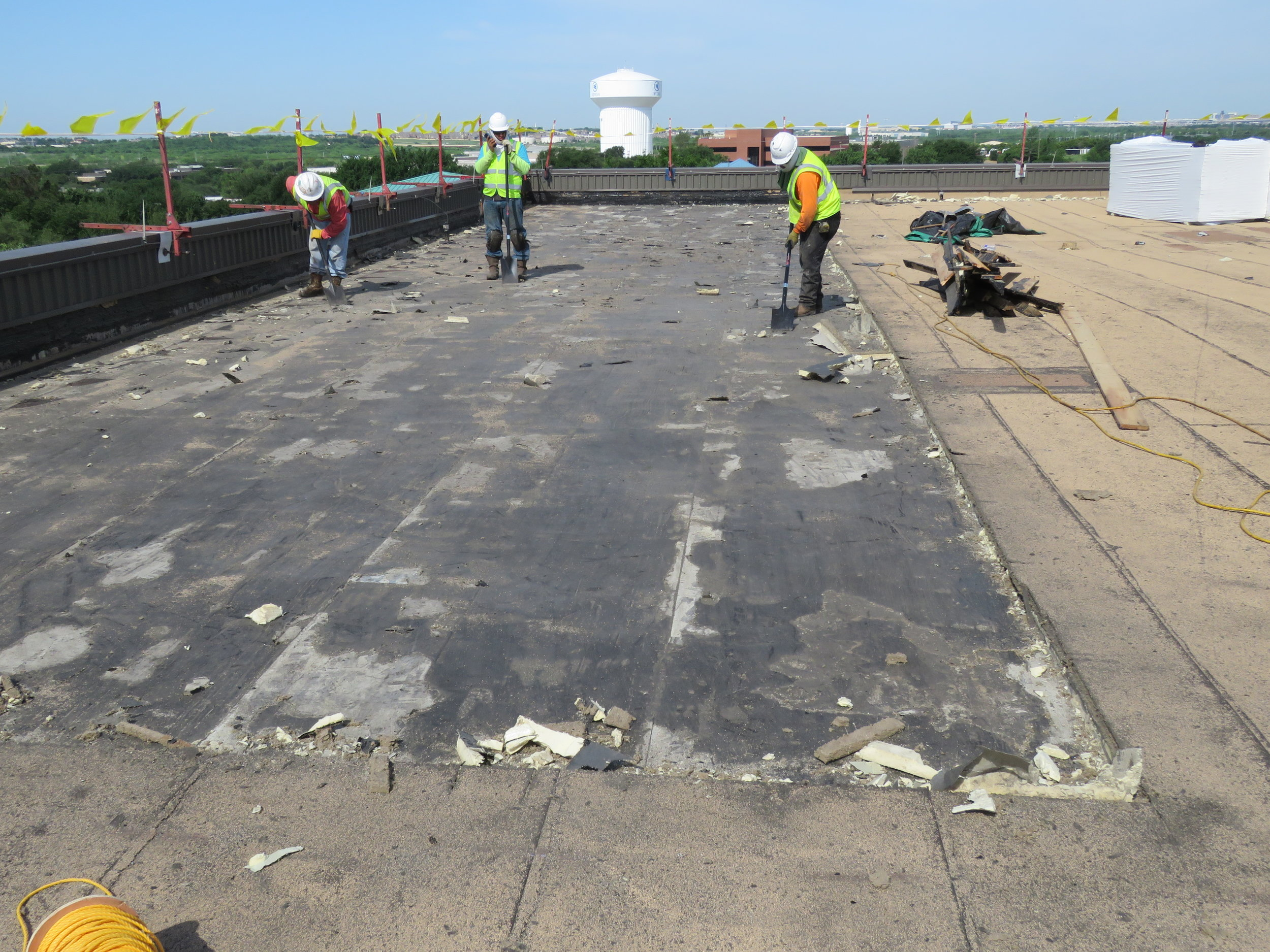 Removing as much of the old vapor barrier as they can.