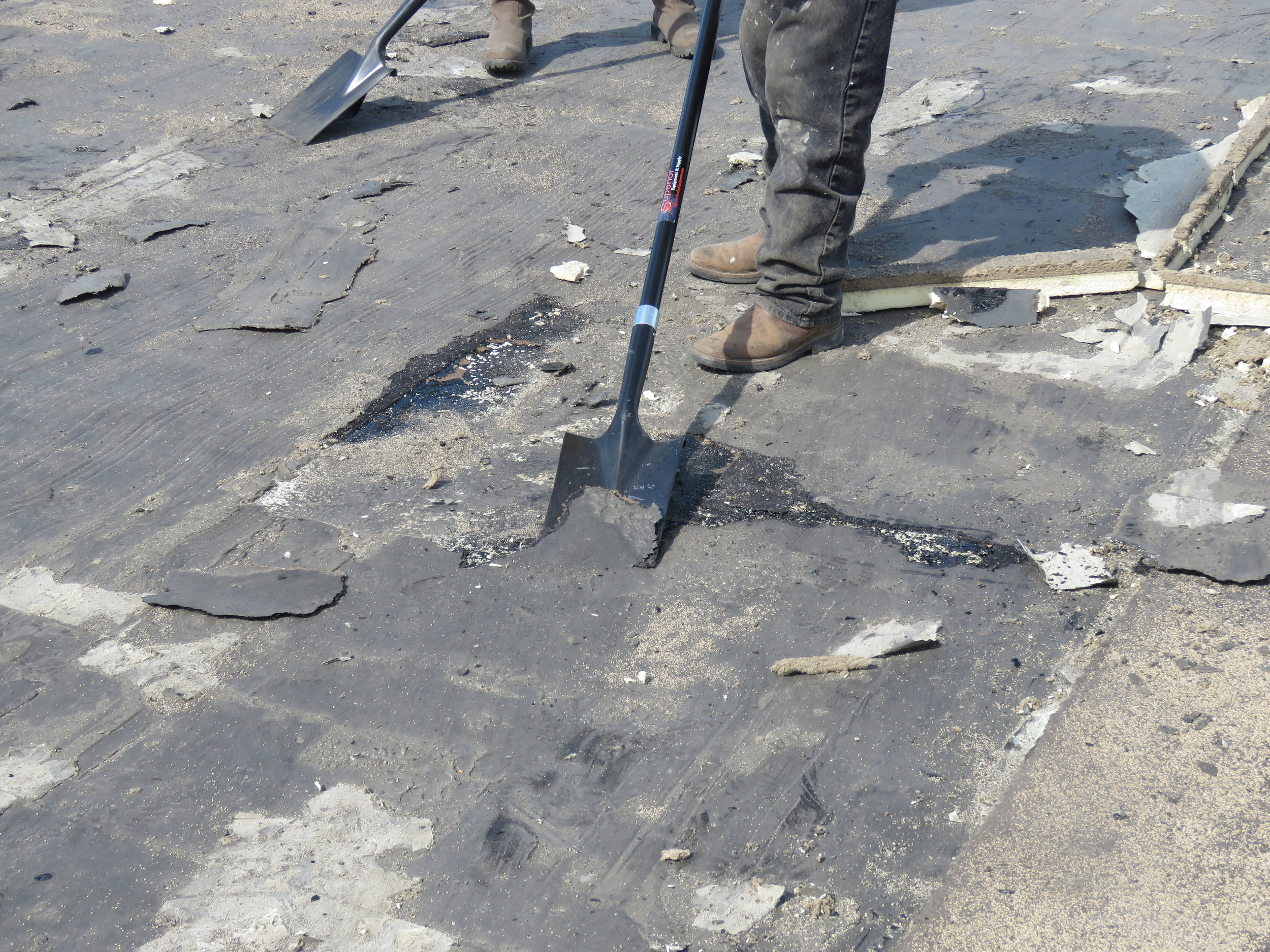The old vapor barrier was attached with hot asphalt, and it's really fused to the concrete deck.