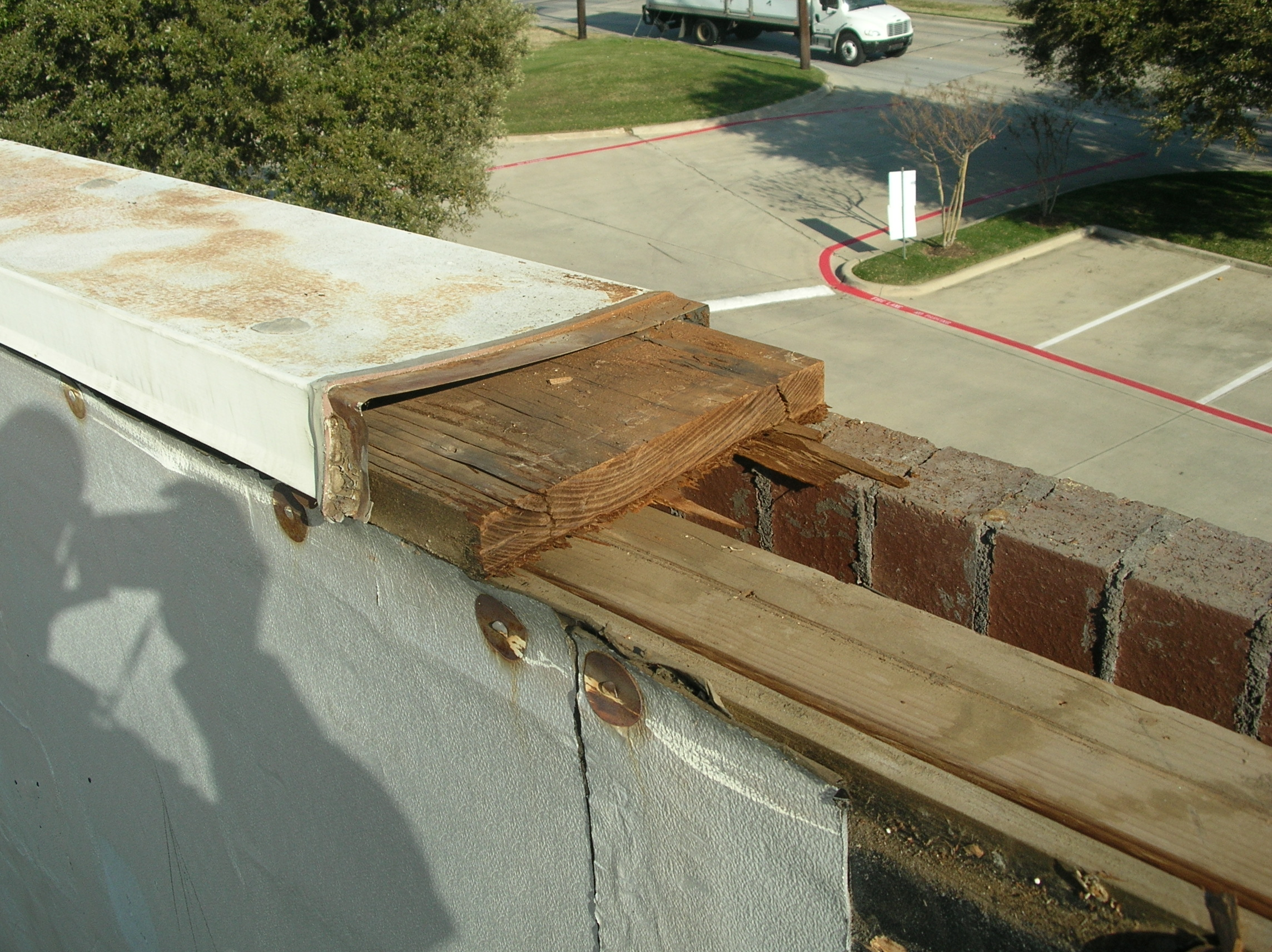 Metal coping, or cap flashing, being removed from a parapet wall.