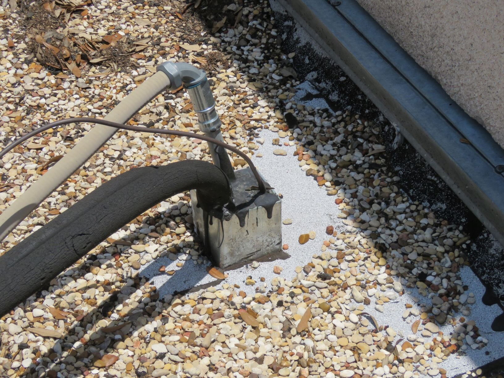 Galvanized steel pitch pan on a built-up roof with various conduit penetrations.