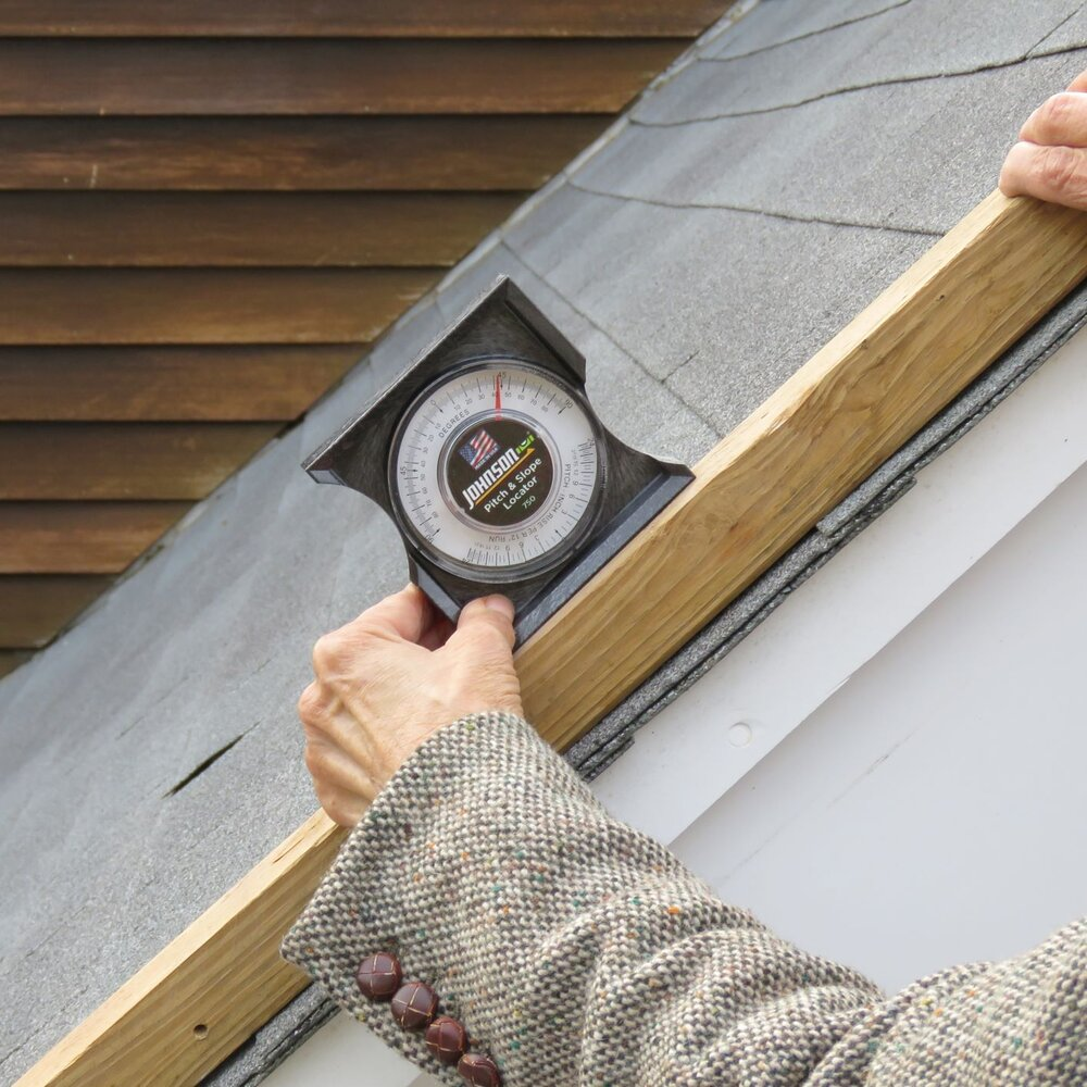 Using a slope finder to find the slope of a roof. It's important to bridge the individual shingles to get an accurate reading.