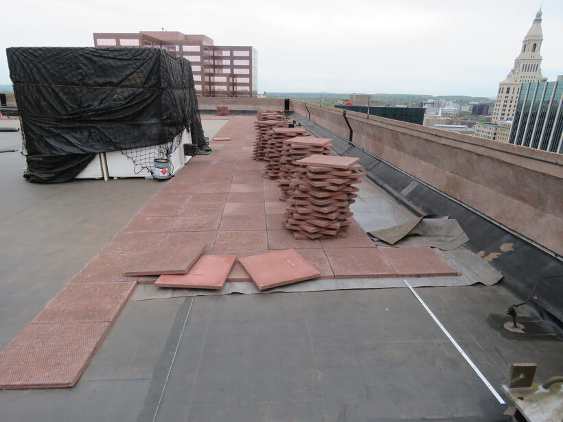 Installing brick-colored concrete pavers for ballast on an EPDM roof.