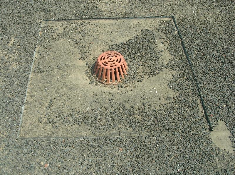 A roof drain on an old built-up roof.