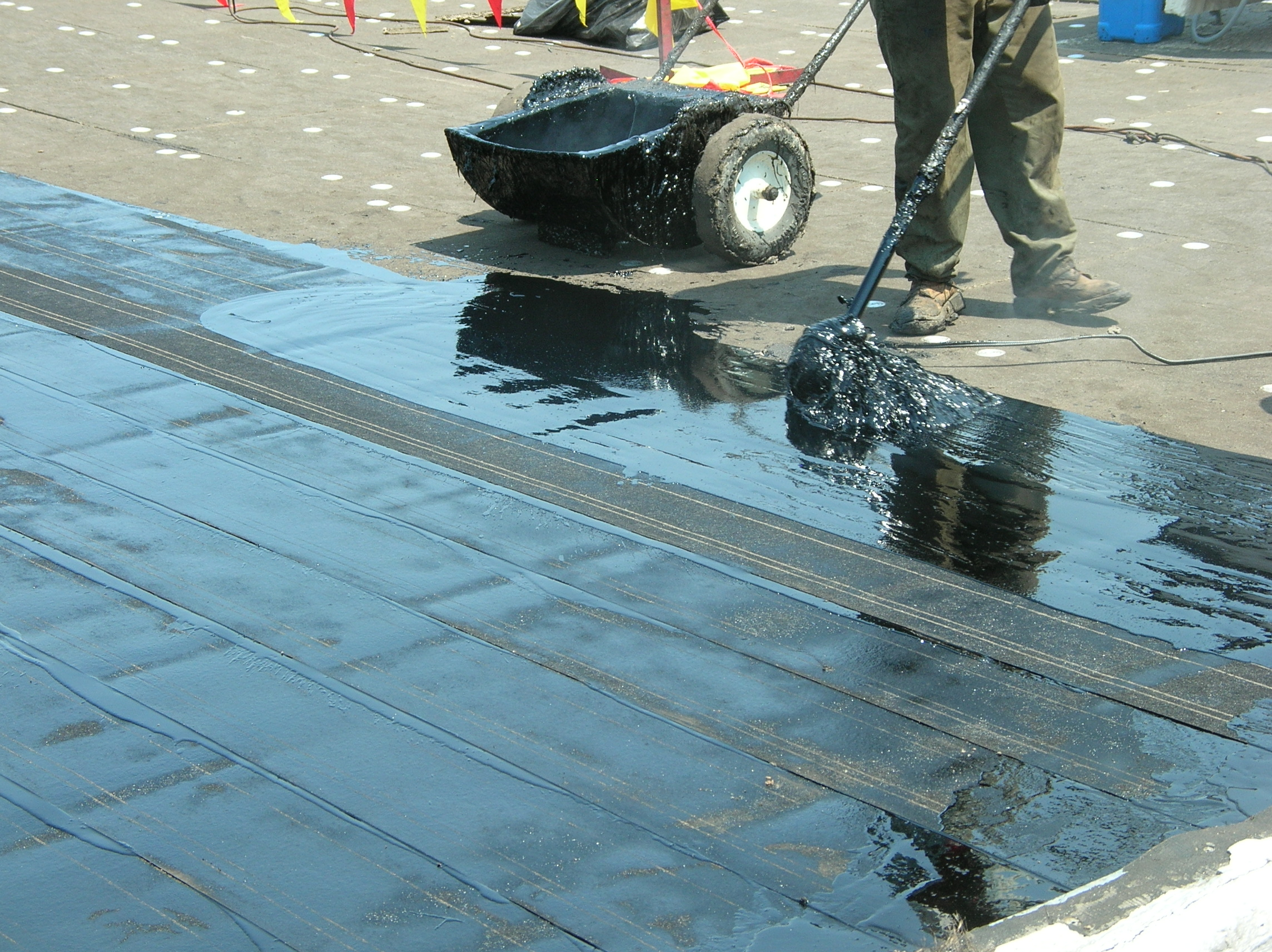Roofing asphalt being applied to a built-up roof: Hot mopping in the field of the roof.